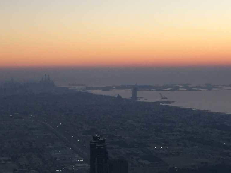 Burj Al Arab and Palm Island in the background from the 148th floor of Burj Khalifa at sunset